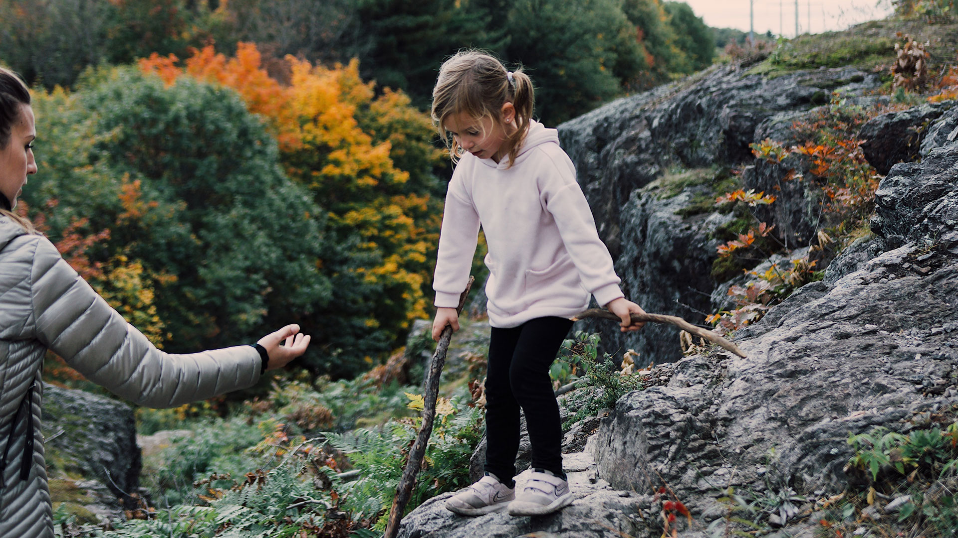 Girl climbing on rocky trail with her mother's help